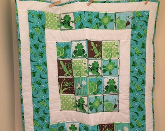 A cute quilt with frogs and turtles.