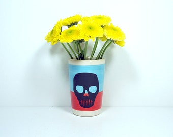 itty bitty cylinder in colour block of sky blue & red-orange, with a voodoo skull on it, made to order.