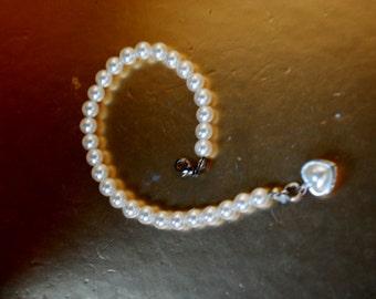 Bridal vintage 80s crisp white faux pearl bracelet ,accented with a heart shape charm. Size 7 1/2