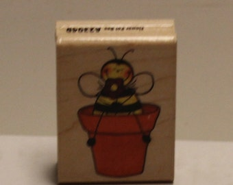 Bee Holding a Flower Sitting on a Pot Rubber Stamp