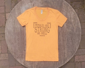 Unbreakable Kimmy Schmidt / Females are STRONG as HELL / Feminist T-Shirt / American Apparel Gold Tee