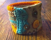 Crocheted cuff with fabric and stitched accents.