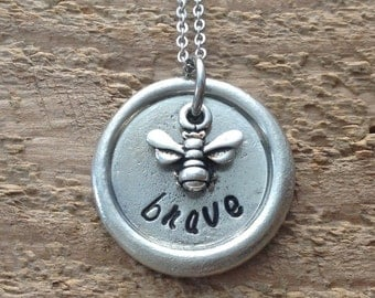 Hand stamped bee brave pewter pebble necklace with bee charm on a stainless steel chain