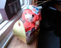 Vintage 1960s to 1970s Hong Kong Raggedy Ann Styrofoam Head Christmas Ornament Hanging Doll On Sled With Presents