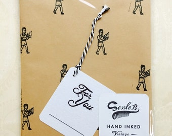 Retro hand stamped wrapping paper and gift tag. Vintage 1950's boy with boat stamp. Black ink on brown paper.