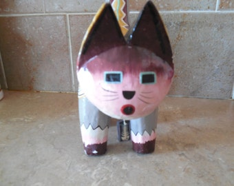 Mexican wood cat with pink cheeks and square eyes long tail.
