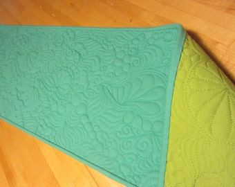 Reversible and intricately quilted teal and chartreuse table runner.  10 3/4 x 44 inches.