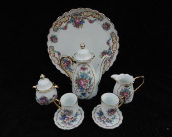 A Child's Toy Tea Pot and Service Set: Porcelain Hand Decorated.