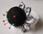 One black felt flower wrist pincushion