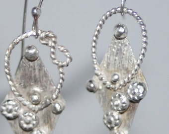 Sterling Silver hand textured earrings adorned with silver flowers.