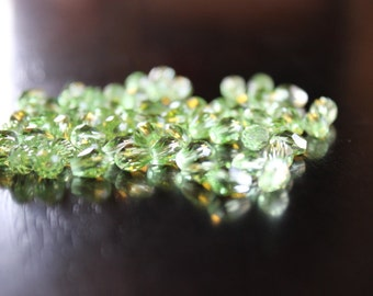 65 transparent glass beads, faceted drop shape, light green, 8 mm x 6 mm x 6 mm, hole 1 mm