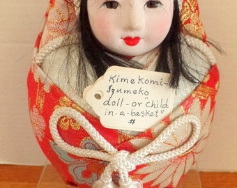 Very nice Asian KimiKomi Himoko or Child in a Basket doll.  She is dressed in red satins, with porcelain head and face