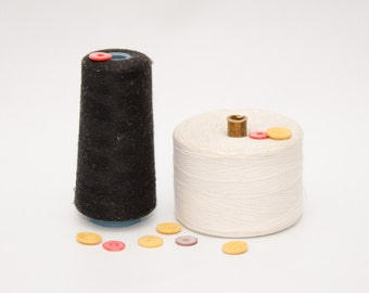 Two spools of thread, black and white, vintage
