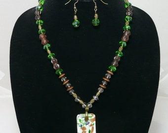 Unique Murano-style glass pendant hangs from a green glass and wood bead necklace