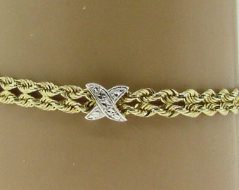 "Sterling silver and 14 K gold X double rope bracelet. 7.5"" long."