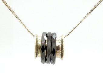 Curvy silver pendant with 3 black ceramic spinners, silver chain