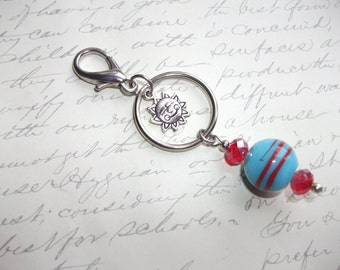 Blue and red keyring with smiling sun charm