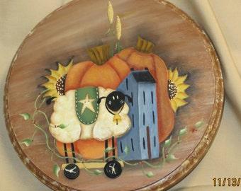 Pumpkins, sheep and blue salt box house on round plaque