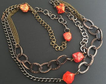 Long mixed metal chain necklace with red howlite nuggets.