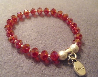 Red crystal rondelle bracelet with 'love' charm