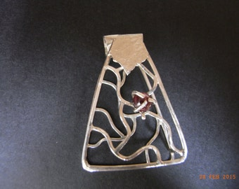 Sterling Silver, cage type pendant with a garnet setting