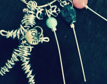 Voodoo doll charm with pins