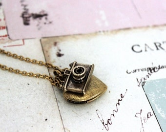 camera. heart locket necklace. in gold ox with etched lines locket
