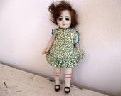 """Vintage Porcelain 6.5"""" Doll with Green Floral Print Dress"""