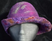Wet felted merino wool and silk sliver fashioned into a very lightweight purple and green cloche style brim hat
