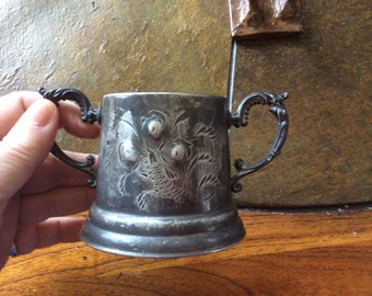 Old vintage double handled cup marked on bottom floral engraving on front
