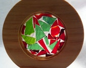 Salvaged cypress round filled with various shades of red and green stained glass.