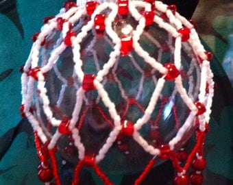 White with red hand beaded ornament cover.