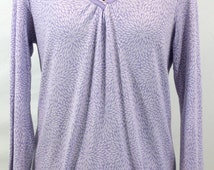 Lavender print top with v-neck and tiny leaf pattern. Embellished with ribbon at neckline hem. By Ellen Tracy
