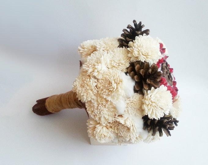 Winter wedding bouquet with pine cones and frozen berries