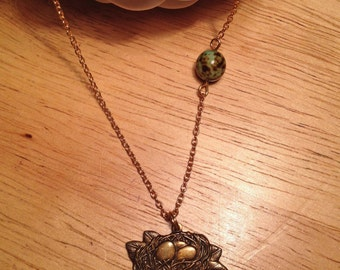 Brass birds nest, vintage green bead necklace on a gold plated chain