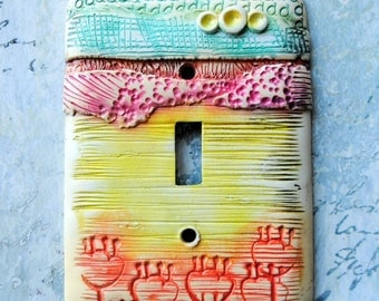 Orange Flowers, light switch cover, polymer clay over metal cover, chalk used for soft effect, orange, yellow, pink, turquoise, abstract