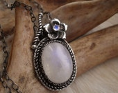moonstone necklace in sterling silver featuring oval blue flash moonstone and round faceted moonstone in a flower