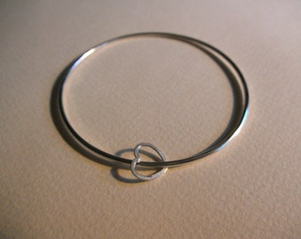 Thin, simple sterling silver bangle with floating heart
