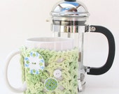 Mug Hug cozy in shades of  green crocheted cotton with coaster bottom and decorative buttons