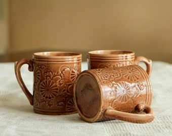 Set of three brown earthy ceramic cups with flower design, vintage coffee mugs
