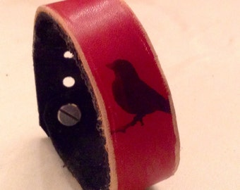 red and brown leather wrist cuff with birds on a wire print