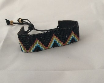 Wide colorful bracelet predominantly black. Closure black leather with waxdraad.