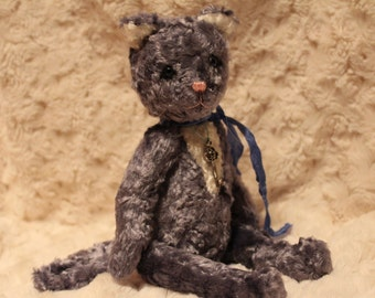 The teddy cat is sewn into the hand on the neck from the house that he is looking for