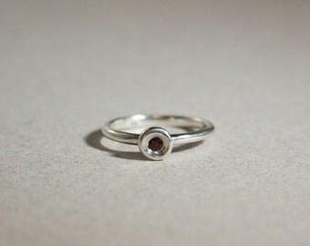 silver organic pod ring with garnet gemstone