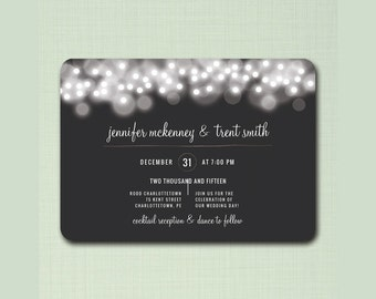 Rustic wedding invitation with sprakly garlands and an elegant cursive font on a charcoal background.