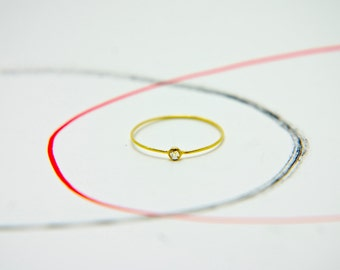 ring made with 18 karat gold wire with round section with small diamond stud