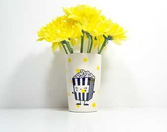 itty bitty cylinder with yellow polkadots and a happy popcorn guy, made to order.