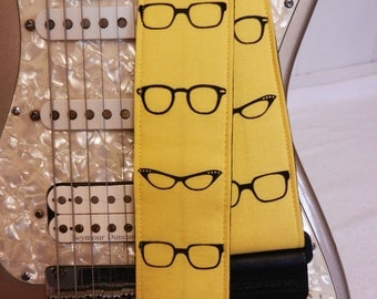 black hipster glasses on yellow indie guitar strap