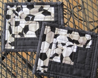 Coasters, set of two, black and white with soccer balls.