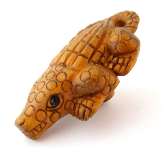 One baby alligator hand carved boxwood ojime bead from
